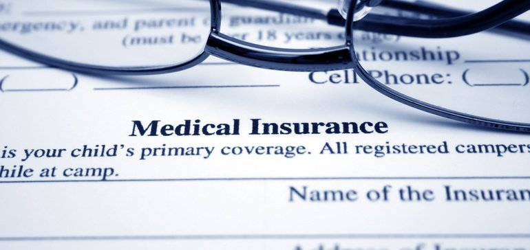 medical insurance form with glasses laying on the form