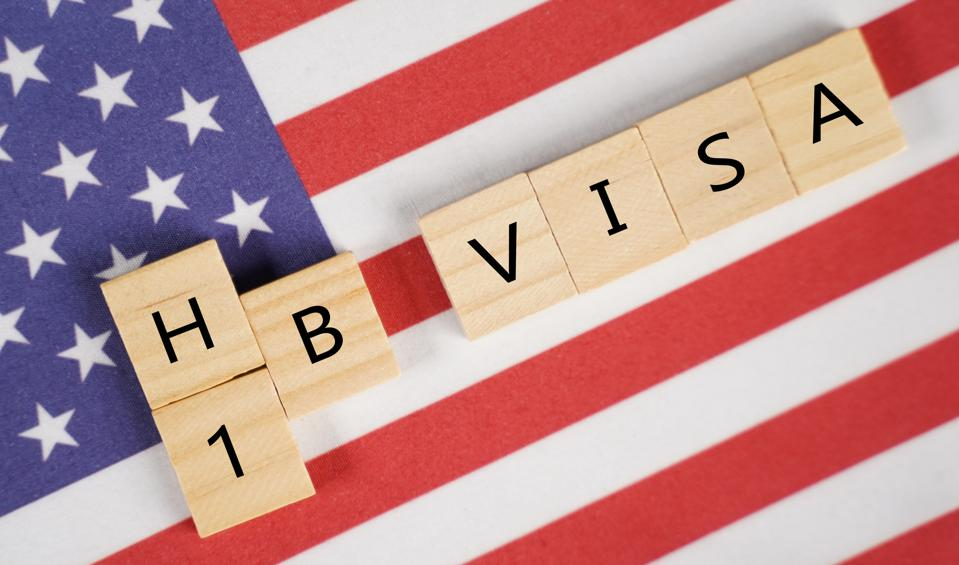 an American Flag with the scrabble letters saying H1B VISA