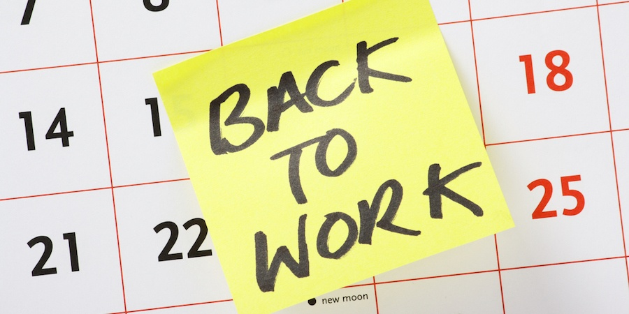a yellow sticky note saying back to work on a calendar