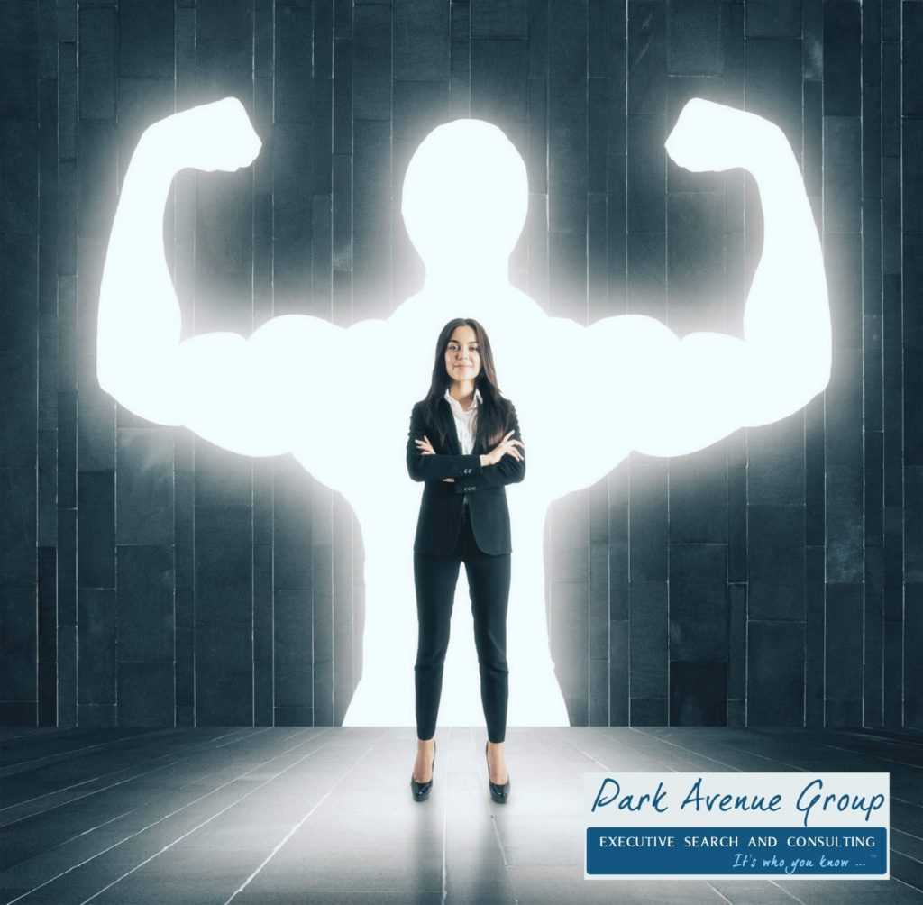 a women standing in a suit with a muscle shadow behind her
