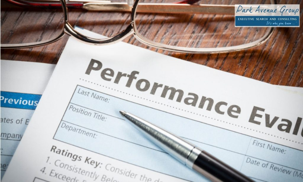performance evaluation paper with a pen on top with glasses next to the form on a brown table
