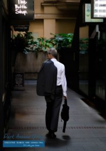 a man walking with his suit jacket on his back