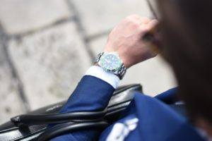 a man looking down at this watch on his wrist