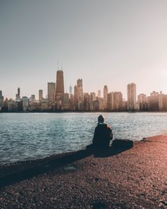 Man sitting on edge of Lake Michigan staring at Chicago Skyline